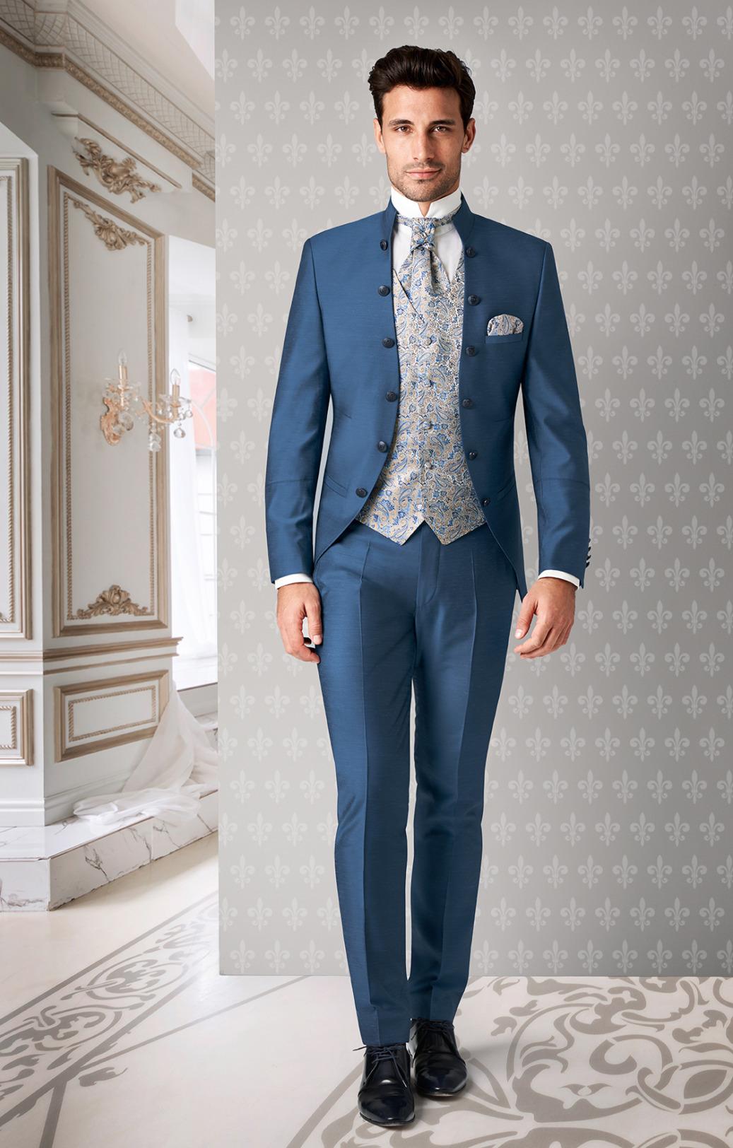 Wilvorst Tziacco Hochzeitsanzug Männer Mode Bräutigam extravagant mittelblau mit Zierknöpfen Stehkragen und gemusterter Weste in creme blau Jabot weisses Hemd mit Stehkragen