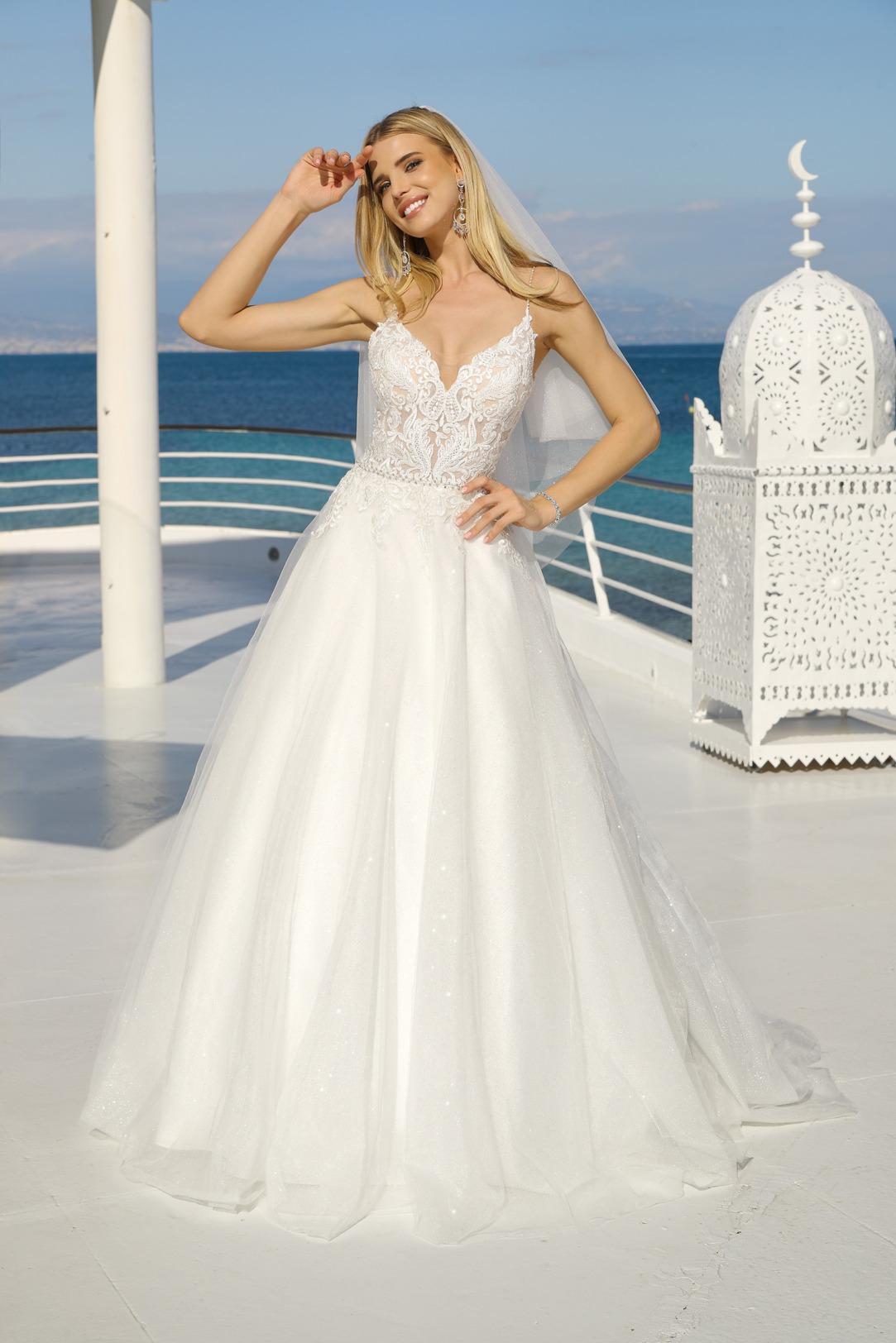 Brautkleid in A-Linie mit tiefem V Ausschnitt und feinem Spitzen Oberteil. Dieses traumhaftschöne Brautkleid hat Spagetti Träger und einen weiten Rock mit Glitzertüll. Hochzeitskleid in A-Linie von Ladybird Modell 321018.