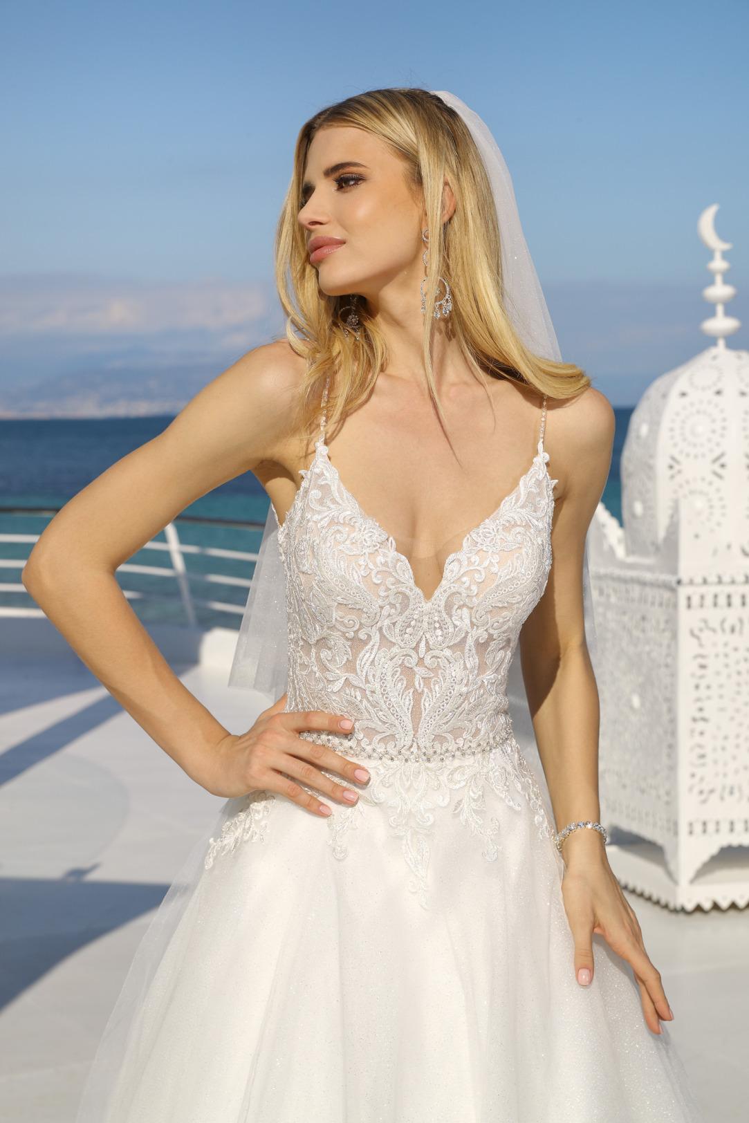 DetailansichtDetailansicht Hochzeitskleid in A-Linie von Ladybird Modell 321018. Brautkleid in A-Linie mit tiefem V Ausschnitt und feinem Spitzen Oberteil. Dieses traumhaftschöne Brautkleid hat Spagetti Träger und einen weiten Rock mit Glitzertüll.