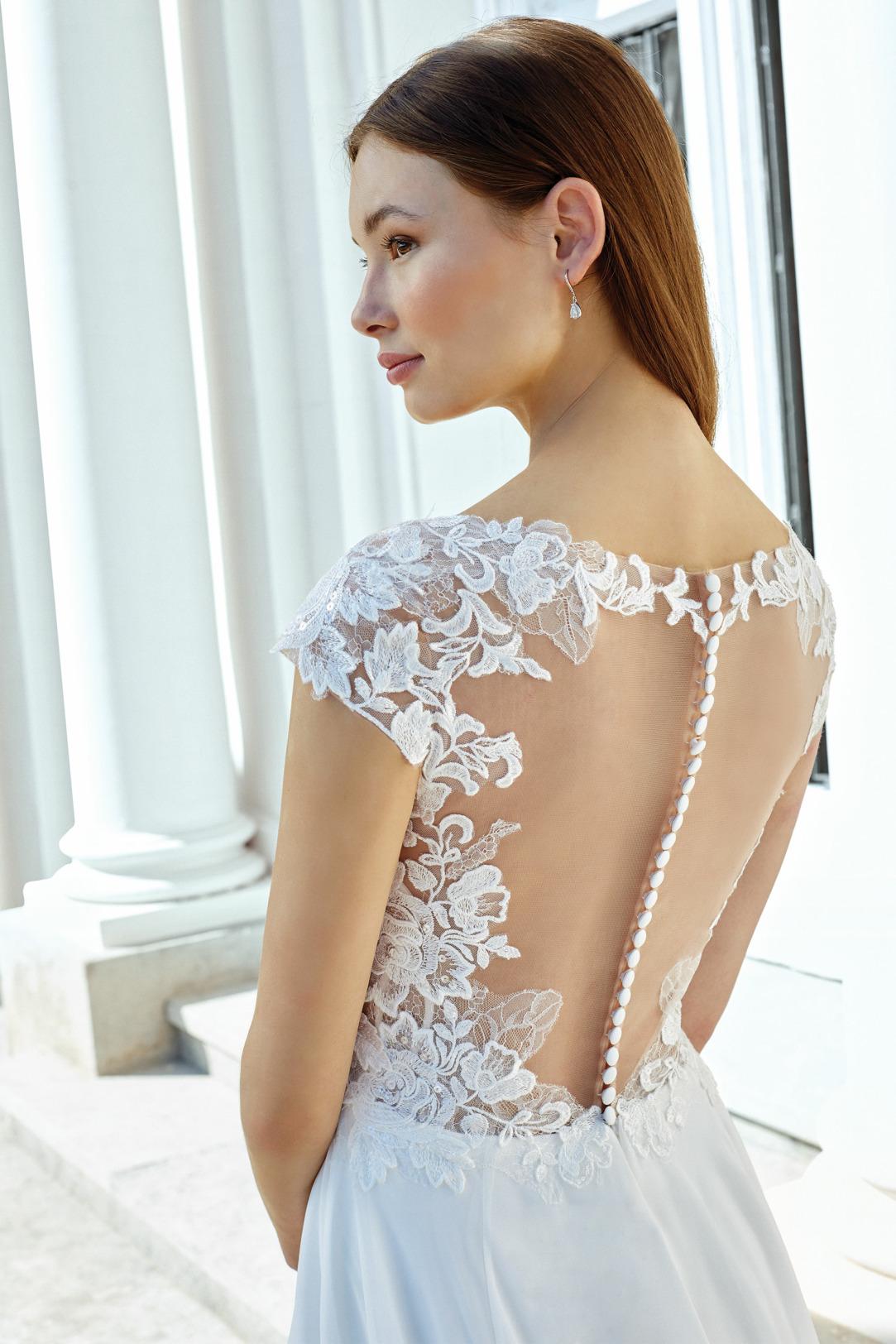 Rückenansicht im Detail - Hochzeitskleid in A-Linie von Adore by Justin Alexander Modell 11123.  Wunderschönes Brautkleid mit V-Ausschnitt und überschnittenem Arm. Hochwertige Spitzen Applikationen und dekorativer Knopfleiste am Rücken weich fließender Chiffon Rock Rückenansicht Detail