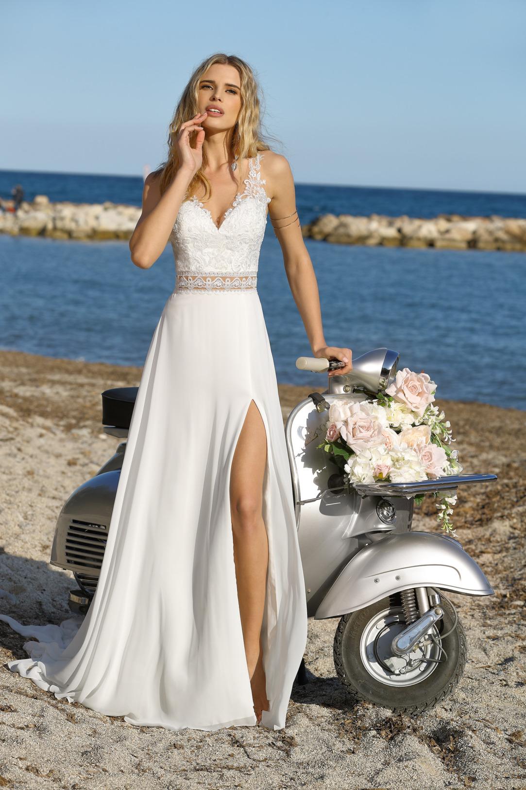 Brautkleid im Vintage Boho Stil.  Ladybivrd Modell 321019 mit V Ausschnitt und Spitzen Trägern.  Hübsches Asseccoire: der leicht transparenter Taillengürtel. Dieses bezaubernde Hochzeitskleid im Empire Stil ist mit und ohne langem Bein Schlitz erhältlich