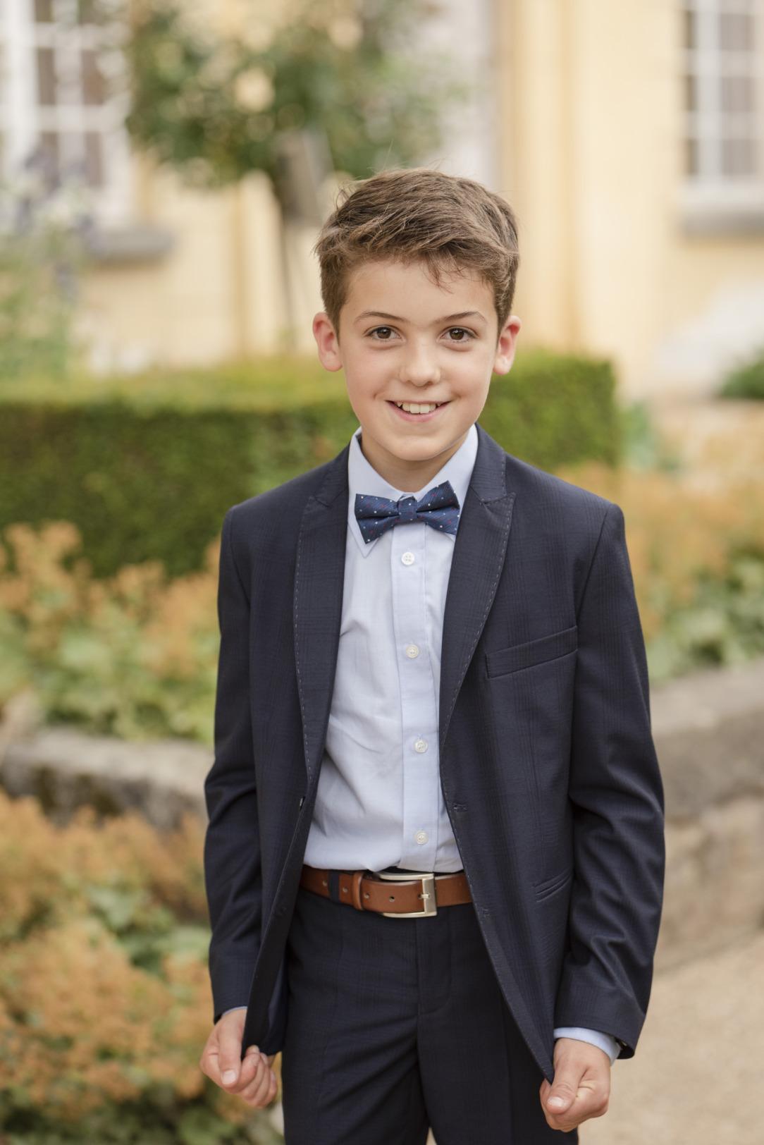 Lässiger Kommunion Anzug für Jungen von Weise Junior - Modell 7516351. Sakko und passende Hose in dunkelblau mit attraktiver Fliege.