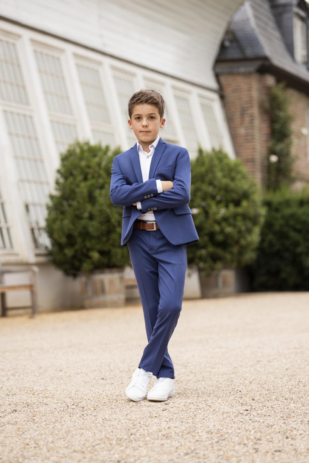 Moderner blauer Kommunionanzug für Jungen von Weise Junior - Modell 7517951. Top modisch - Super sportliches Outfit: Der mittelblaue Kommunionanzug kombiniert mit weißen Turnschuhen.