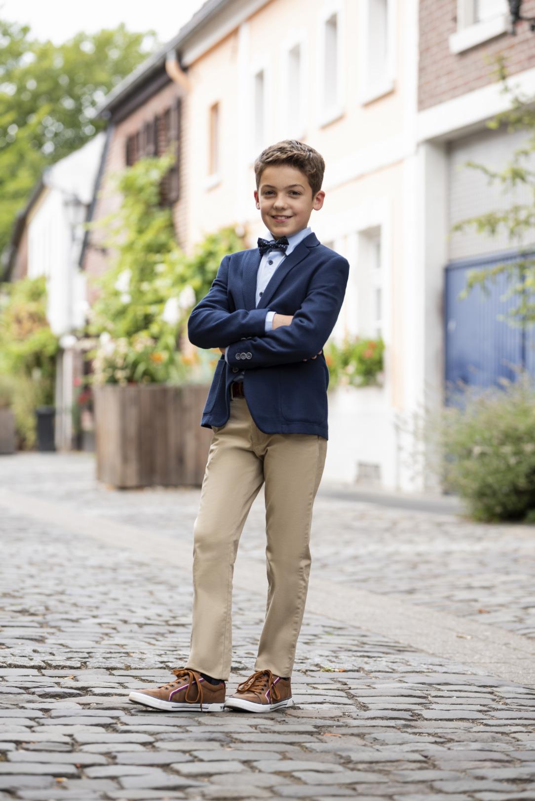 Moderner Kommunionanzug für Jungen von Weise Junior - Modell 7527701. Das dunkelblaue Sakko hat einen hohen Stretchanteil für die Bequemlichkeit. Hier kombiniert mit einer beigen Jeans. Lässig - modern - sportlich und elegant in einem.